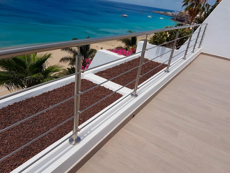 Barandilla exterior de aluminio para terraza, realizada con pasamanos y barrotes en tubo de aluminio redondeado