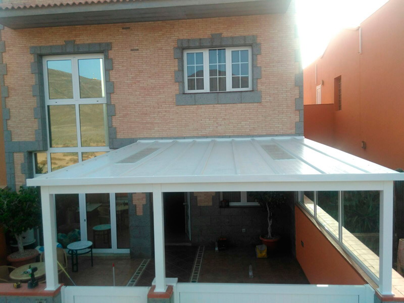 Vista del techo de aluminio blanco para este cerramiento de ampliación. También tiene unos ventanales fijos y puerta peatonal a media altura