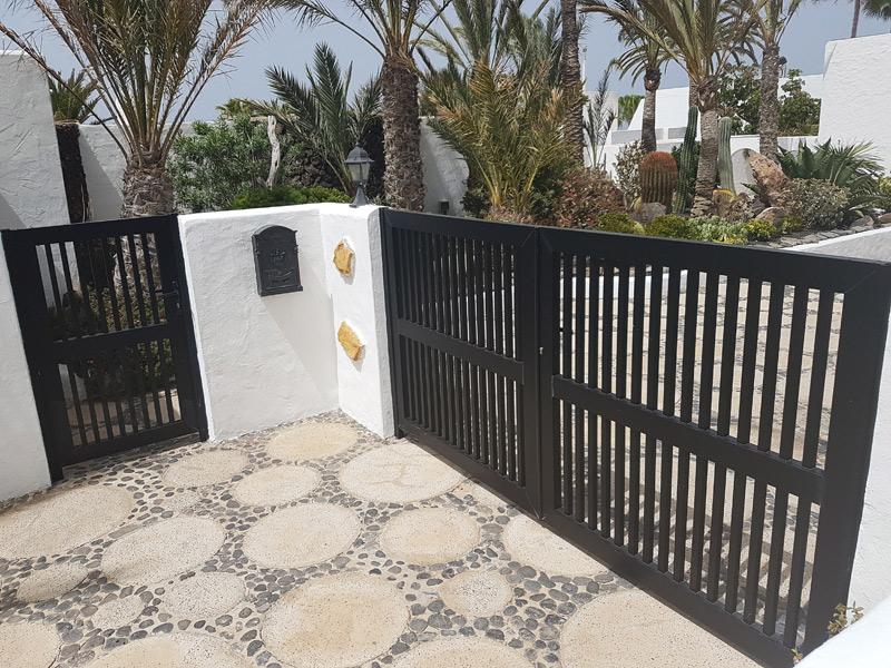Puerta peatonal con diseño clásico de barrotes de aluminio y portón de acceso también en aluminio negro mate