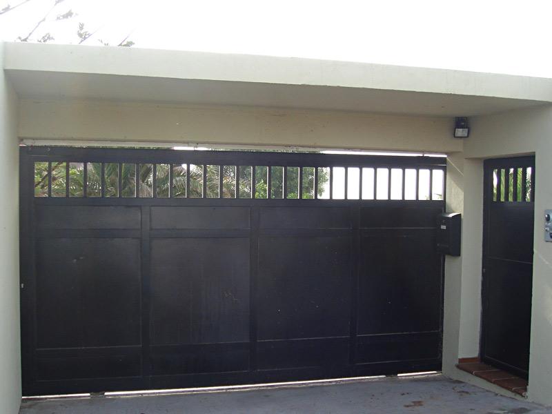 Puerta peatonal exterior y portón de entrada en aluminio negro mate