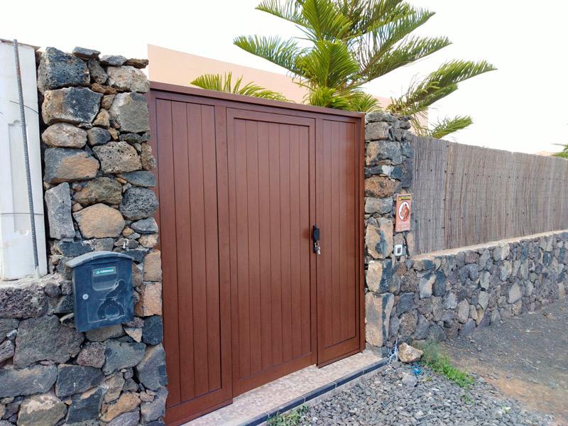 Puerta peatonal de exterior realizada en aluminio imitación madera